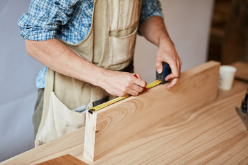 Home repair concepts. Custom-made Furniture Concept. Handicraft Carpentry. Cabinet-maker hands measuring a wooden plank using tape-line on the working table in the workshop, close up.