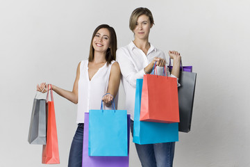 Two beautiful female friends on shopping with colorful bags. Toothy smile two young women portrait