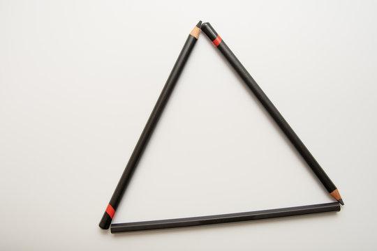 Three black pencils forming a triangle