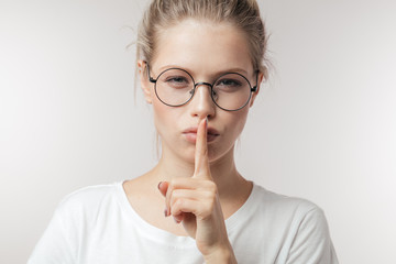 Cute mysterious girl wearing eyeglasses in casual outfit showing silence sign holding forefinger on lips, or having a big secret isolated on white background