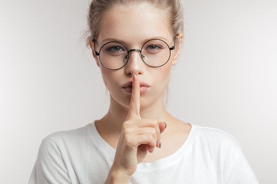 Finger on lips - silent gesture. Caucasian young woman in round spectacles holding her finger to her lips calling to keep silence, close up.