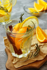 Cold ginger tea with orange and lemon in glass cups. Tea with ice. The decor. Cinnamon and Rosemary Spices