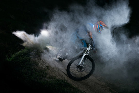 A cyclist on a mountain bike with dusty aggressive turns. Downhill riding at dark night. Bicyclist on a bicycle.