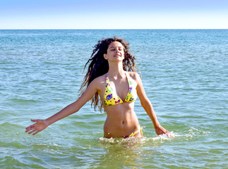 Beautiful long hair female model wearing bikini, posing in the water, outdoor portrait