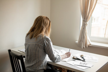 Back rear view Portrait of young beautiful lady sitting at white desk and think about calligraphy