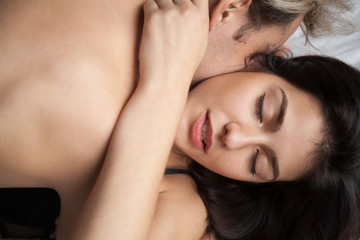 Close up head shot of young heterosexual couple in love having passionate sex. Portrait of attractive lover brunette young woman face and shirtless naked man lying in bed. Passion desire love concept