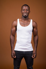 Handsome muscular African man against brown background