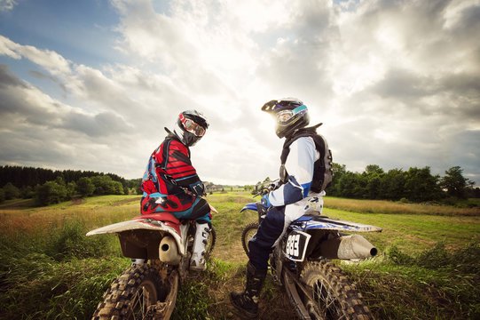 Bikers sitting on motorcycles at field against cloudy sky