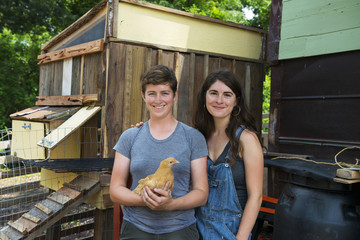 Portrait of homosexual couple holding chicken while standing at farm