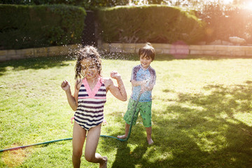 Boy spraying water with hose pipe on girl in garden