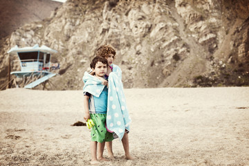 Siblings wrapped in towel at beach