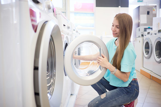 Young woman choosing washing machine in the appliance store