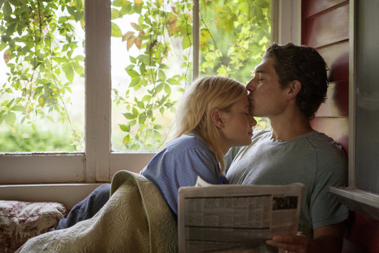 Man kissing woman's forehead by window at home