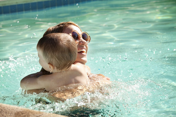 Mother embracing son in swimming pool