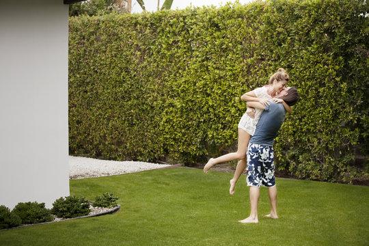 Man lifting woman on lawn