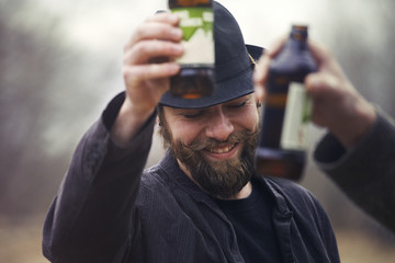 Happy man toasting with bottle outdoors