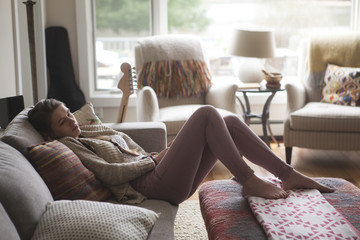 Full length of thoughtful girl relaxing on sofa at home
