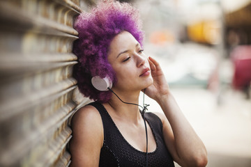 Woman looking away while listening music outdoors