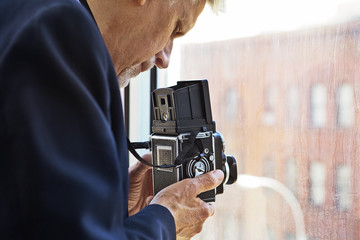 Senior man photographing with old fashioned camera at window