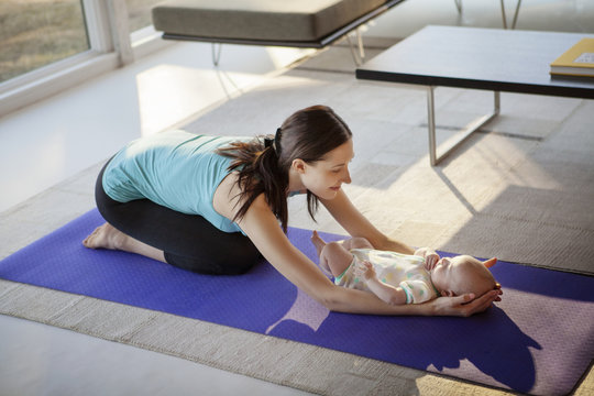 Woman holding baby girl while kneeling on exercise mat
