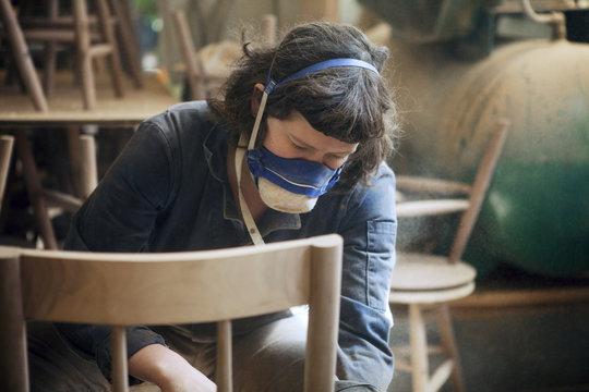 Carpenter examining wooden chair at workshop