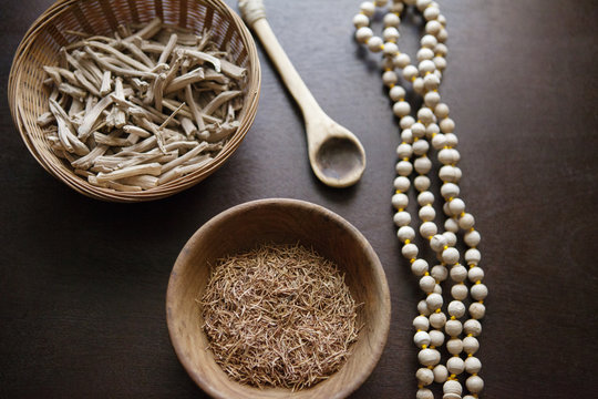 High angle view of herbs in bowls with prayer beads on table