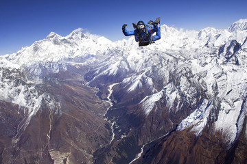 Man skydiving against snowcapped mountains