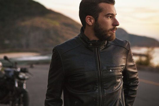 Man in leather jacket standing on coastal road
