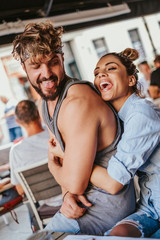 Smiling girlfriend hugging boyfriend from behind in a cafe