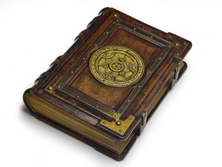 Large luxury leather - wooden book with a gilded transmutation circle in center of the front cover, attributed to a German alchemist from the 17th century. It laying on the table, angled on the righ.
