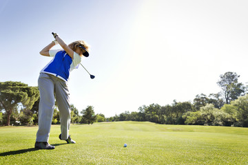 Senior woman playing golf against clear sky
