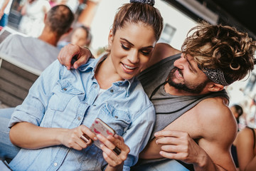 Smiling girlfriend showing mobile phone to her boyfriend