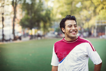 Happy soccer player looking away while standing at field