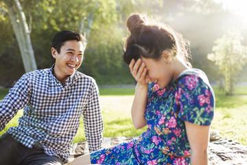 Happy couple sitting on grassy field