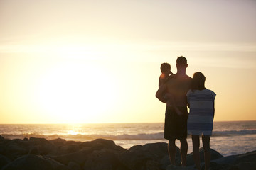 Rear view of family standing at beach during sunset