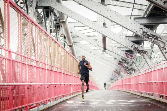 Male athlete jogging at pedestrian walkway