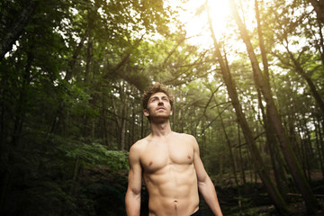 Shirtless man looking away while standing in forest