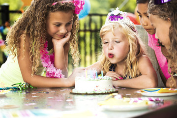 Friends looking at girl blow candles