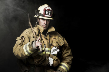 Firefighter looking away while holding shovel