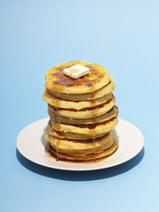 Stack of pancakes in plate against blue background