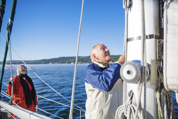 Senior man tying rope in sailboat on sea against clear blue sky