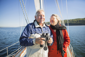 Happy senior man holding binoculars while standing with woman in yacht on sea