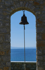 The bell at front with the still sea and the blue sky with the clear horizon on the background on Skiathos island in Greece