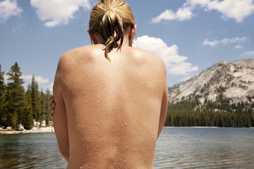 Rear view of shirtless woman standing in lake