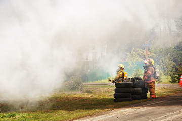 Firefighters standing by stack of tires