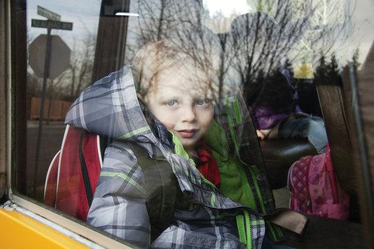 Portrait of smiling boy seen through school bus window