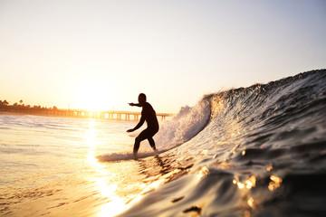 Man surfboarding on wave in sea against bridge