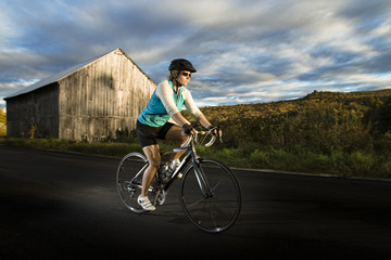 Woman cycling on road by old barn