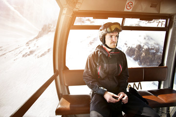 Thoughtful man sitting in ski lift over snowcapped mountain