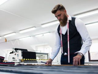 Young bearded man tailor working on new clothing